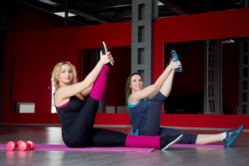 Two smiling girls do stretching exercises on mats in fitness cen