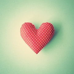 Red patterned cotton heart over blue background