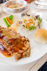 Grilled steaks,bread and vegetable salad