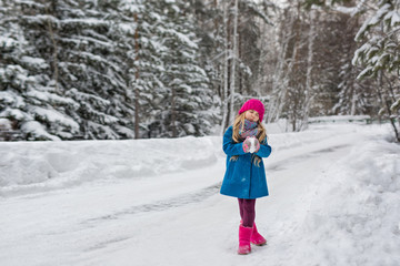 Little girl grimacing in the winter forest