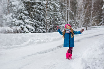 Little girl hamming and playing in the winter forest