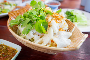 Slice steamed fish with fried garlic topping and spicy sauce.