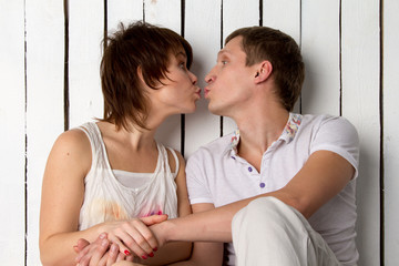 Young couple is kissing near the white wooden wall