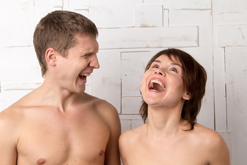Young couple with emotions of laughtering near the white wall