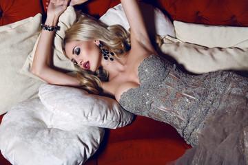 gorgeous woman in elegant dress lying on red divan
