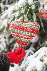 knitting heart on fir-tree branch with hand in red glove