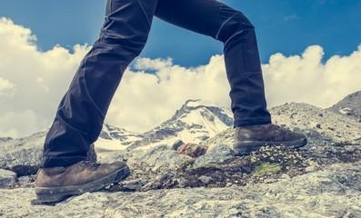 Close-up of hiking shoes on mountain ridge.