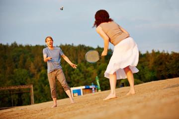 Paar spielt Federball am Strand im Sommer