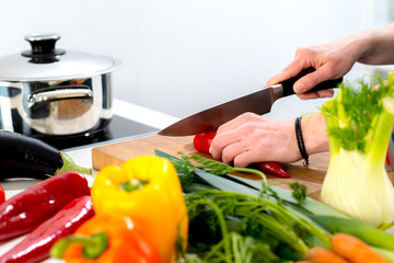 womans hand cutting vegetables