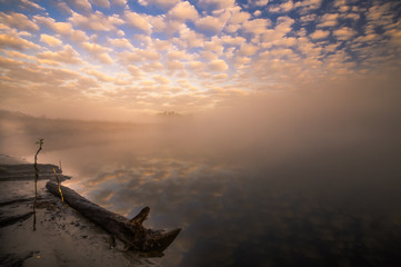 misty morning on the river and clouds reflected in water