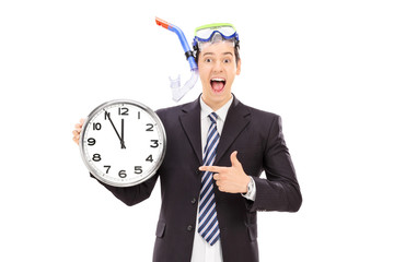 Joyful businessman with a snorkel holding a big clock