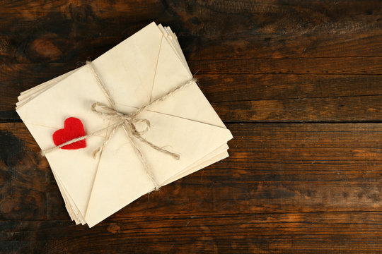 Stack of love letters on rustic wooden planks background