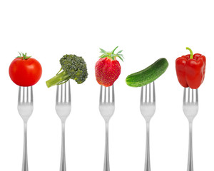Healthy diet, organic food on forks with vegetables and berries.