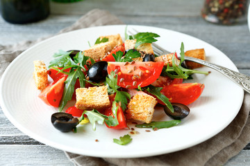 Summer salad with tomatoes and arugula, olives