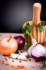 garlic, onion fresh herbs on old wooden board