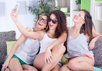 A group of three female friends having fun with smartphones