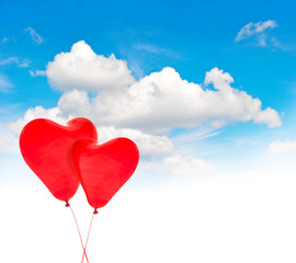 Heart shaped red balloons in blue sky. Valentines Day background