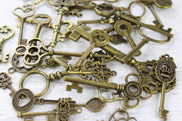Pile of antique brass keys on a distressed wood background.