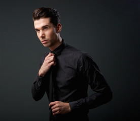 Cool young man in black shirt and tie