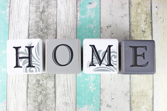 Home sign on a distressed wooden background with turquoise tones