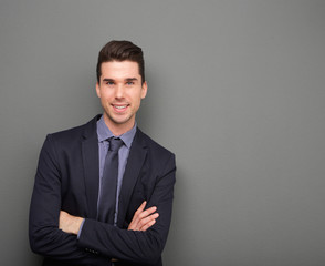 Handsome young business man smiling with arms crossed