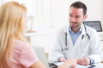 Young attractive doctor taking notes while patient speaking