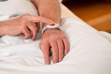 Senior mit Rufhilfe Notfall Telefon im Bett