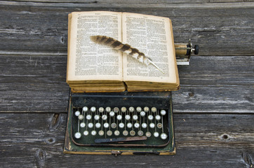 typewriter with old book Bible and bird feather on keyboard