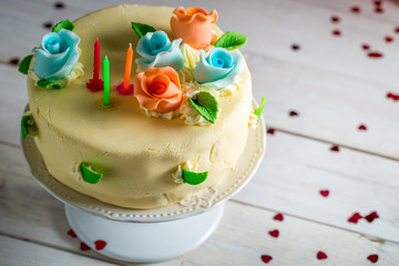 Birthday cake with candles and sugar roses