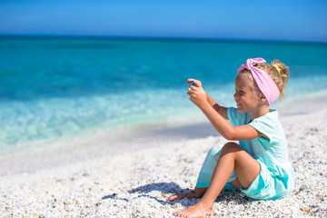 Little cute girl taking pictures on phone at tropical beach