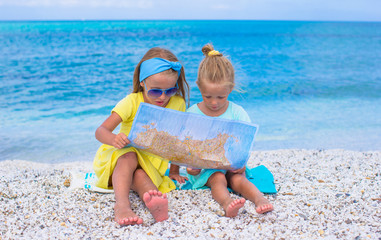 Adorable little girls with map of island on tropical beach