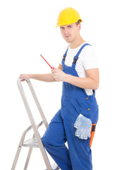 young man builder in blue coveralls with screwdriver on ladder i