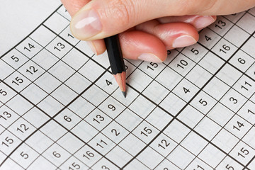 woman hand holding a pencil and solves crossword sudoku