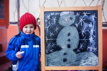 Adorable little boy, drawing winter picture with chalk