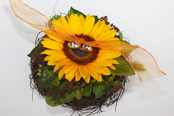 Wedding rings on bouquet with single yellow sunflower