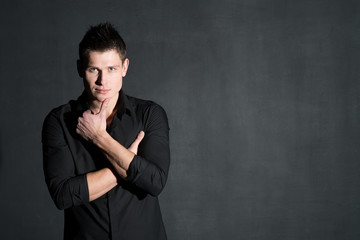 Young attractive man in black shirt on dark background