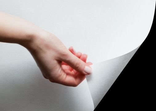 Hand pulling a paper corner to uncover, reveal something