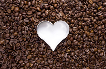 Hundreds of coffeebeans with a heart cutter