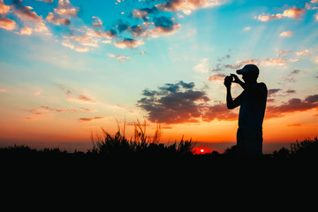 Silhouette Of Young Man Photographing The Sunset On Smartphone