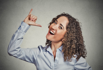 Woman showing let's drink hand gesture grey wall background