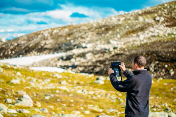 Young Man Taking Pictures Of Norwegian Mountain Landscape On Tab