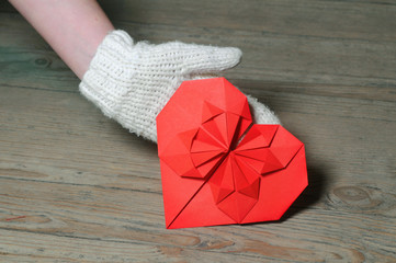 Origami heart in hand on wooden background