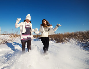 Two girlfriends have fun at beautiful winter day