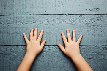 Children's hands is located on an old wooden plate