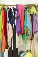 Untidy messy cluttered woman wardrobe with colorful clothes.
