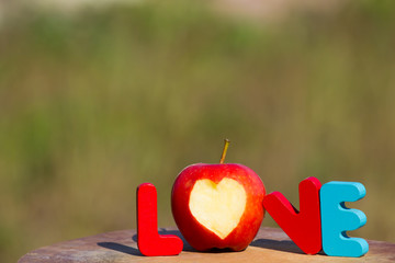 Colorful Wooden word love with apple heart on wooden table on me