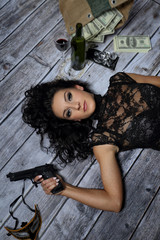 Young girl with a gun money and a bottle of wine
