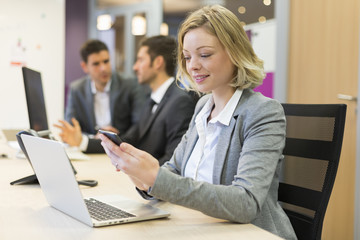 Cute businesswoman on mobile phone in office, sms, message
