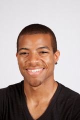 Black man in black shirt smiling at the camera