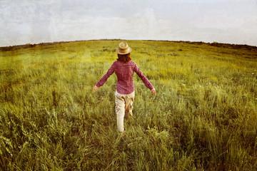 Woman walking on summer meadow, vintage image